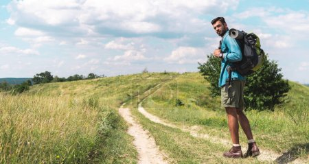 Photo for Traveler with backpack walking on path on green meadow - Royalty Free Image