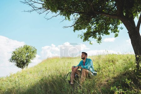 young traveler with backpack sitting on green summer meadow