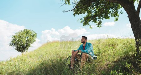 handsome traveler with backpack sitting on green summer meadow