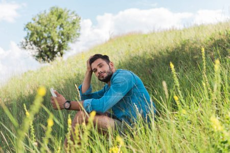 Photo for Male traveler using smartphone on green summer meadow with tree - Royalty Free Image