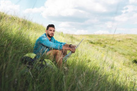 male traveler sitting with backpack and map on green meadow