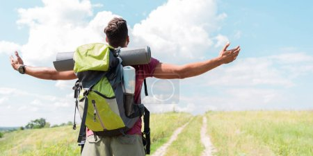 back view of traveler with backpack standing with outstretched hands on green meadow with cloudy sky
