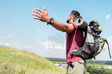 traveler with backpack standing with outstretched hands on summer meadow with blue sky