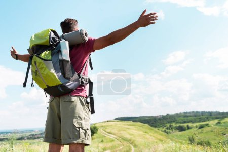 tourist with backpack standing with outstretched hands on summer meadow with cloudy sky