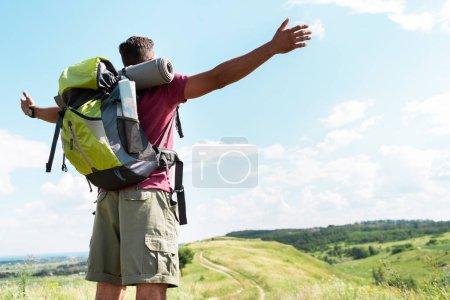 Photo pour Touriste avec sac à dos debout avec les mains tendues sur la prairie d'été avec ciel nuageux - image libre de droit