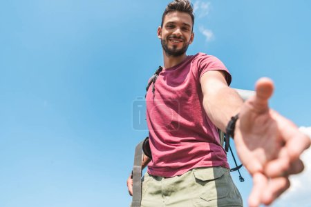 bottom view of handsome young tourist stretching out hand, blue sky on background