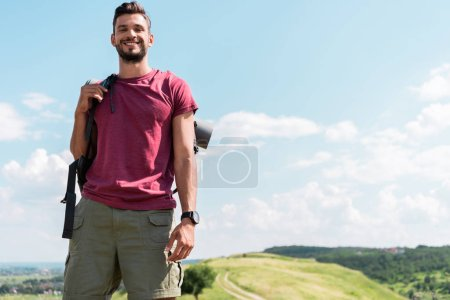 smiling young hiker with backpack standing on green meadow with blue sky