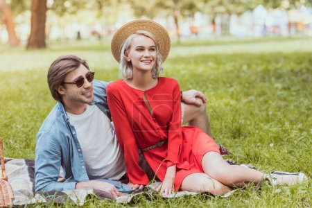 smiling couple sitting on blanket in park and looking away