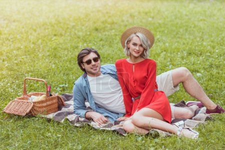 Photo for Couple sitting on blanket in park and looking at camera - Royalty Free Image