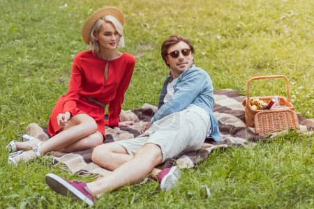 Photo for Couple sitting on blanket in park and looking away - Royalty Free Image