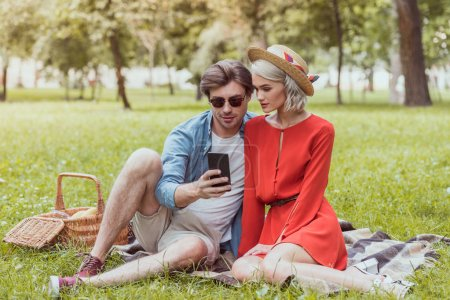 couple sitting on blanket in park and using smartphone