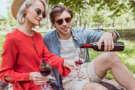 boyfriend pouring red wine in glasses from bottle in park