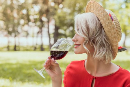side view of attractive girl in red dress drinking red wine in park