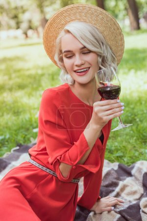 Photo for Attractive girl in red dress holding glass of red wine in park - Royalty Free Image