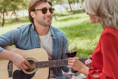 Photo for Handsome boyfriend in sunglasses playing acoustic guitar for girlfriend at picnic - Royalty Free Image