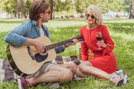 Photo for Handsome boyfriend playing acoustic guitar for girlfriend with wine at picnic - Royalty Free Image
