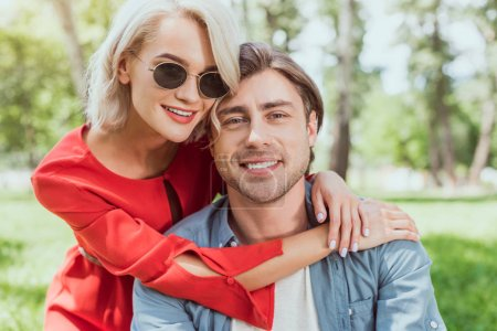 portrait of smiling couple hugging in park and looking at camera