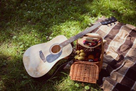 Photo pour Panier pique-nique avec des bananes et guitare acoustique dans le parc - image libre de droit