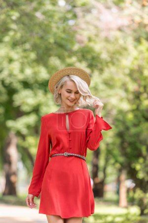 smiling beautiful girl in red dress and straw hat walking in park