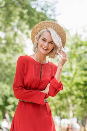 smiling attractive girl in red dress and straw hat looking at camera in park