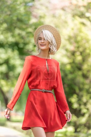 smiling attractive girl in red dress and straw hat looking away in park