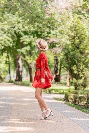 Photo pour Élégante jeune fille en robe rouge et chapeau de paille debout sur la route dans le parc - image libre de droit