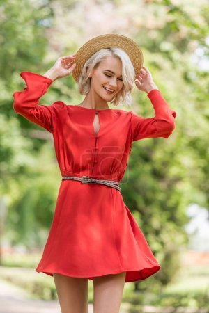 stylish attractive girl in red dress and straw hat posing in park