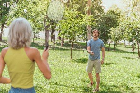 Photo pour Couple, jouer au badminton dans parc de verdure en été - image libre de droit