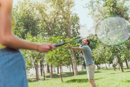 cropped image of couple playing badminton in park in summer