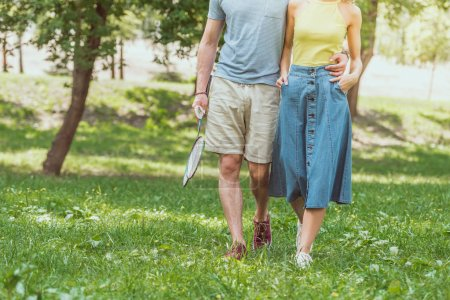 cropped image of couple walking with badminton rackets and shuttlecock to play in park