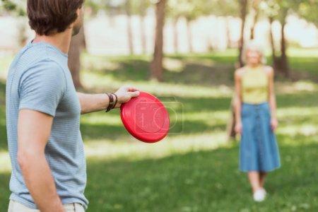 Foto de Pareja joven, jugar frisbee con rojo disco de frisbee en el Parque - Imagen libre de derechos