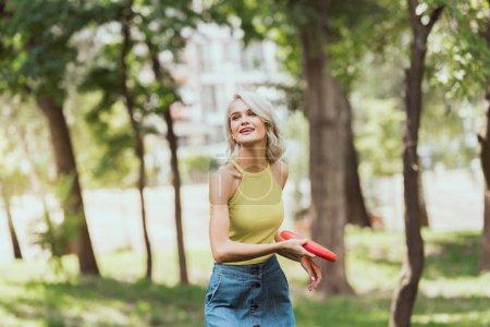 Photo pour Jolie fille blonde, lancer de disque de frisbee dans le parc - image libre de droit
