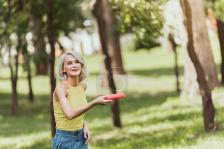 Photo for Beautiful girl throwing frisbee disk in park - Royalty Free Image