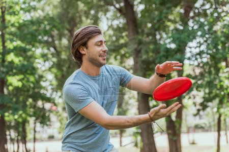 Photo pour Bel homme attraper le disque de frisbee dans le parc - image libre de droit