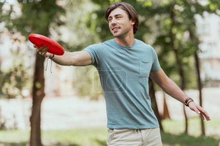handsome man throwing frisbee disk in park