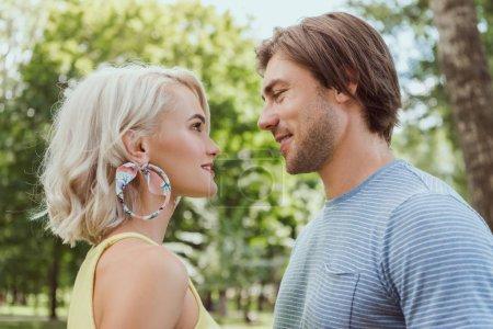 Photo pour Vue latérale du couple se regardant dans le parc - image libre de droit
