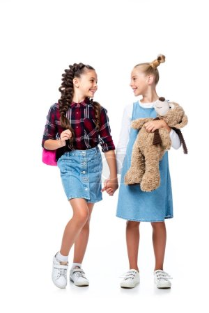 Photo for Schoolchildren holding hands and looking at each other isolated on white - Royalty Free Image