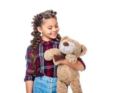 smiling schoolchild holding teddy bear isolated on white