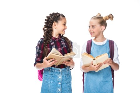 schoolchildren holding open books and looking at each other isolated on white