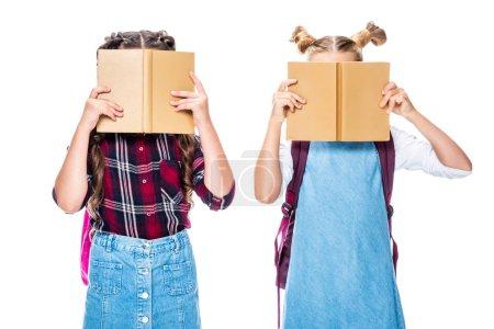 Photo pour Camarades de classe couvrant les visages avec des livres isolés sur blanc - image libre de droit