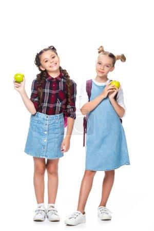 Photo pour Écoliers tenant des pommes et regardant la caméra isolée sur blanc - image libre de droit