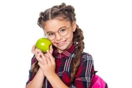 adorable schoolchild holding ripe apple and looking at camera isolated on white