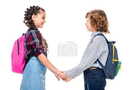 Photo pour Vue de côté de camarades de classe tenant par la main et en regardant l'autre isolé sur blanc - image libre de droit