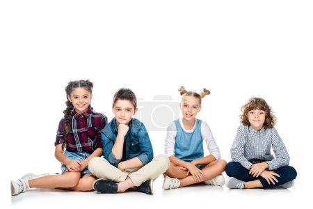 four schoolchildren sitting and looking at camera isolated on white