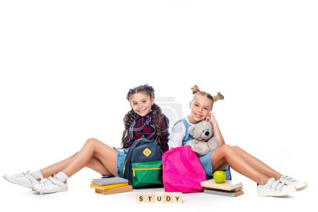 schoolchildren sitting with backpacks and wooden cubes with word study isolated on white