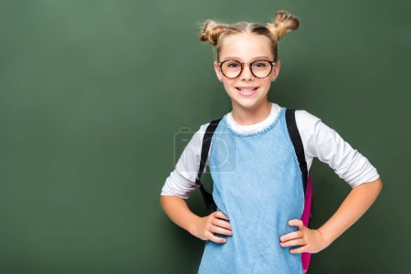 smiling schoolchild in glasses posing near blackboard