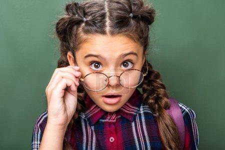 surprised schoolchild looking at camera above glasses near blackboard