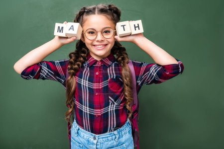 smiling schoolchild holding wooden cubes with word math near blackboard