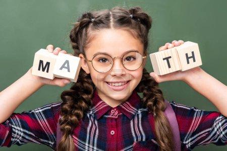 Photo pour Portrait de l'écolier tenant des cubes en bois avec math mot près de tableau noir - image libre de droit