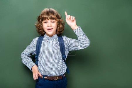 schoolboy showing idea gesture near blackboard